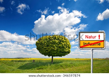 Field,tree and blue sky with sign with german text: nature / industry, environmental protection concept - stock photo