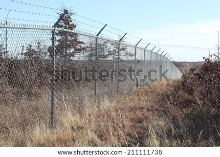 Field with a large wire fence - stock photo