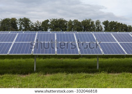 Field with blue siliciom solar cells alternative energy to collect sun energy - stock photo