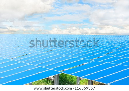 Field with many solar cells with green grass in front of a blue sky with clouds