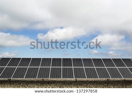 Field with many solar panels in front of a blue sky