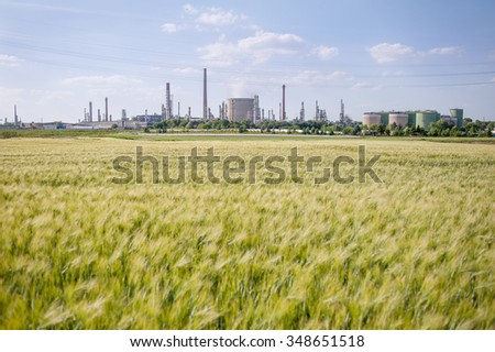 Field with petrochemicals in the background