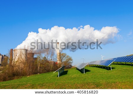 field with solar collectors and fossil-fuel power station - stock photo