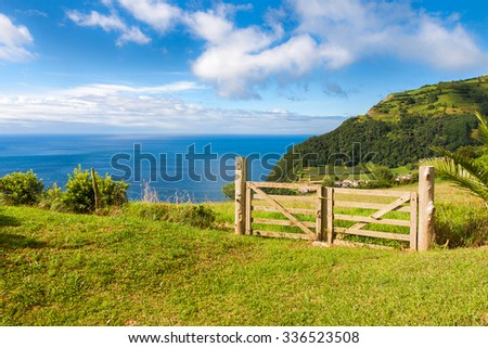 Fields and fence over Atlantic Ocean in Sao Miguel, Azores Islands - stock photo