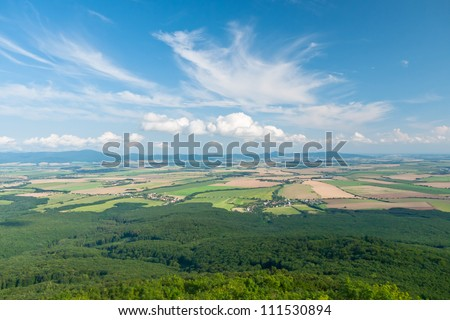 Fields in the lowland area surrounded by forests and mountains - stock photo