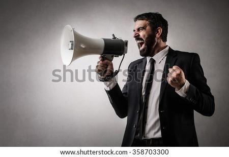 Fierce employee with a megaphone - stock photo