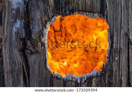 Fiery hole in an old tree stump - stock photo