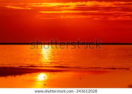 Fiery orange sunset sky over the sea - stock photo