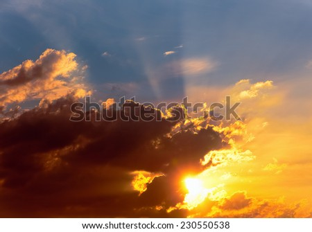 Fiery orange sunset sky with clouds and sun. - stock photo
