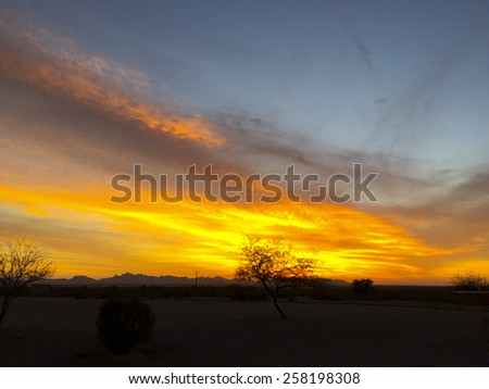 Fiery sky and clouds above Arizona desert at dusk, Tonopah, AZ - stock photo