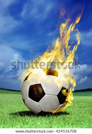 fiery soccer ball on green field