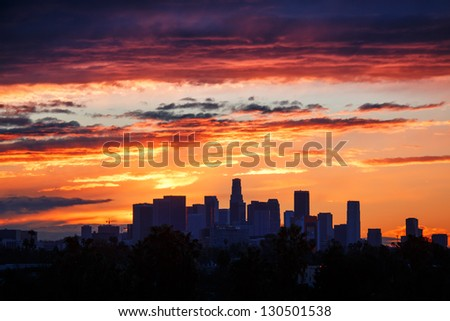 Fiery sunrise clouds over downtown Los Angeles city skyline. - stock photo