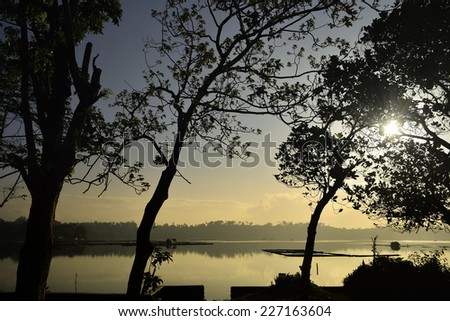 Fiery Sunrise over lake of a fishing and farming village in the Philippines. - stock photo