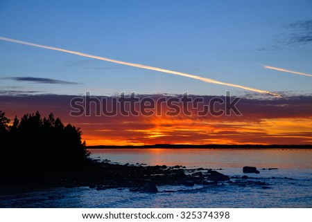 Fiery sunset and trail of the aircraft. Lake Pongoma, North Karelia, Russia - stock photo