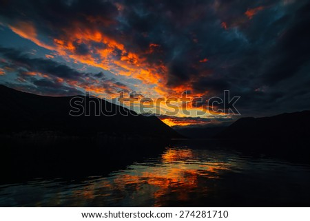 Fiery sunset in the mountains. Bay of Kotor in Montenegro. View from Dobrota. Sunset in Montenegro - stock photo