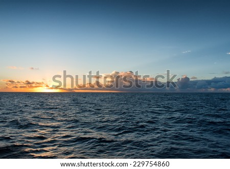 Fiery tropical ocean sunset over a calm blue sea as the glowing orange sun drops below the horizon and low cloud cover - stock photo