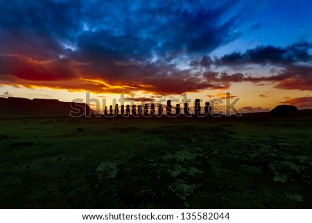Fifteen moais against dramatic blue and orange sky in Easter Iskand - stock photo