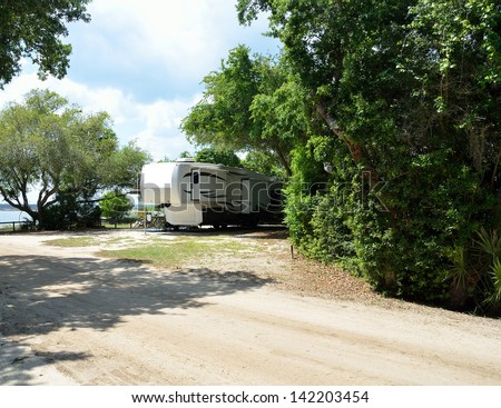 Fifth wheel camper parked at a  camping site along the river's edge at Florida. - stock photo