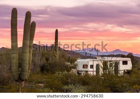 Fifth Wheeler RV parked on campsite in Sonoran Desert beside Saguaro Cacti - stock photo