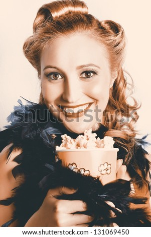 Fifties Pinup Woman Holding Old Popcorn Box Overflowing With Buttered Popcorn When Seeing A Classic Movie In A Depiction Of The Retro Cinema Era - stock photo