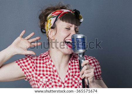 fifties singer in studio - passionate young female rocker with retro style singing live in old fashioned microphone, gray background - stock photo
