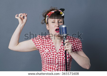 fifties singer in studio - passionate young female rocker with retro style snapping her fingers, singing in old fashioned microphone, gray background - stock photo