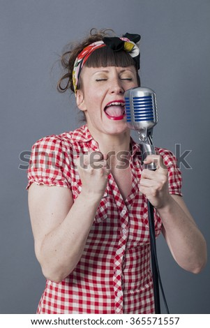fifties singer in studio - passionate young woman with retro style singing in old fashioned mike, gray background
