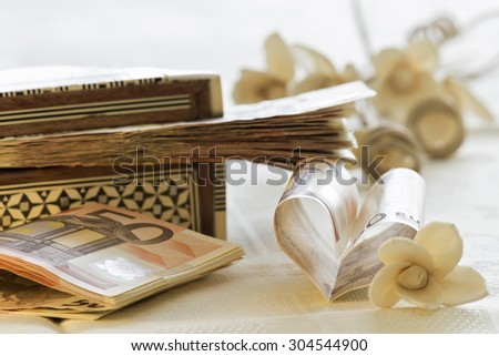 Fifty euro banknotes, gift box and flowers bounquet - stock photo