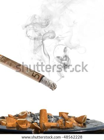 fifty euro cigarette with ashtray and smoke on white background - stock photo