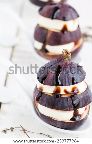 Fig appetizer with mozzarella and thyme, under the balsamic sauce.selective focus - stock photo