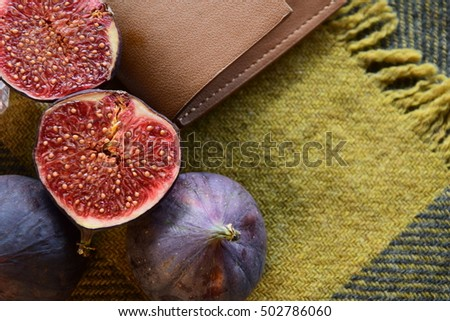 Fig fruit and brown leather autumn composition on the green wool scarf