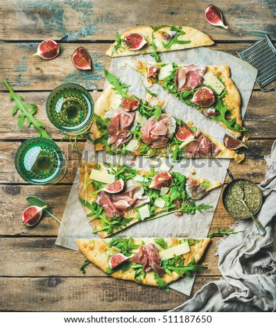 Fig, prosciutto, arugula and sage flatbread pizza cut into pieces with glasses of rose wine over rustic wooden background, top view