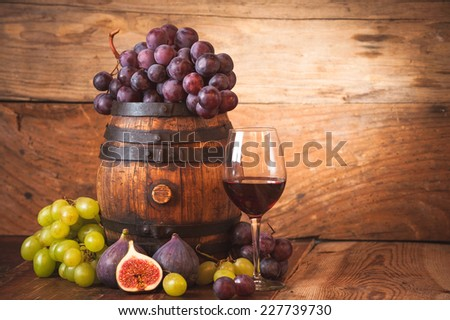 Fig with red wine, grape and barrel on rustic wood tabel - stock photo