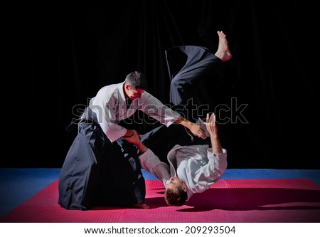 Fight between two aikido fighters on black - stock photo