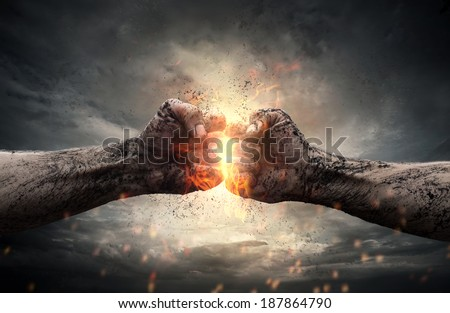 Fight, close up of two fists hitting each other over dark, dramatic sky - stock photo