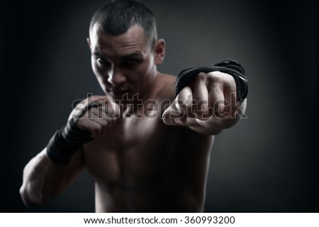 Fighter boxer and warrior's fist on black background - stock photo