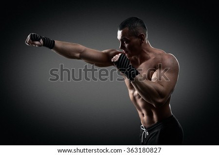 Fighter boxer standing staring strong on black background. Young masculine caucasian male athlete.