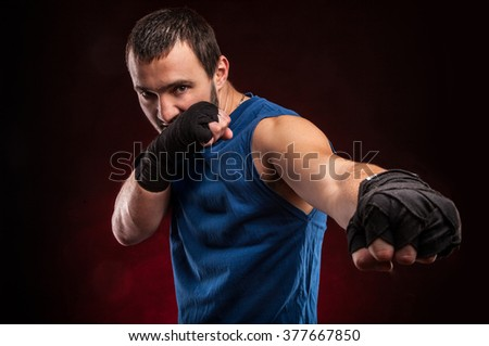 Fighter boxer standing staring strong on red background. Young masculine caucasian male athlete.  - stock photo