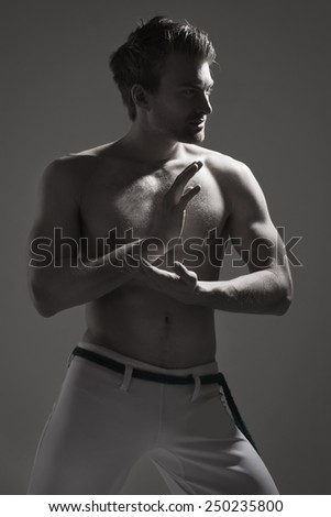 Fighter doing warm up stretch. Low key - stock photo