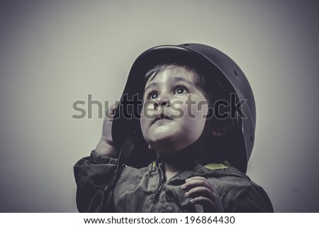 fighter, fun and funny child dressed in military cap, playing war games - stock photo