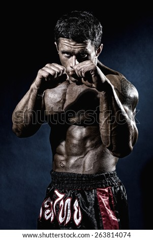 Fighter in a rack with fists. Portrait of a kick-boxer. - stock photo