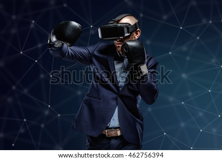 Fighter in a suit with virtual reality glasses device on his head over futuristic background.