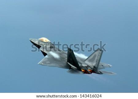 Fighter Jet Plane making Pass through blue sky - stock photo