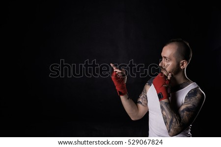 Fighter man show by finger on free space. Portrait of fitness man with white shirt and red boxing bandage. Thinking face emotion.