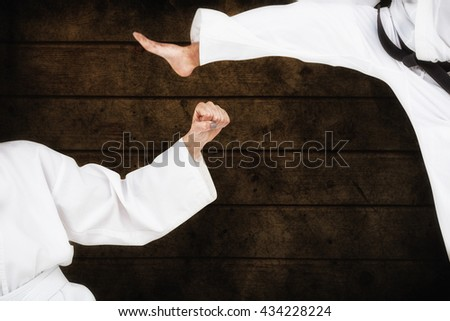 Fighter performing karate stance against dark fence - stock photo