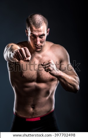 fighter posing shirtless and with bare knuckles on dark background - punch pose - stock photo