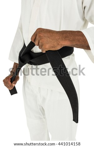 Fighter tightening karate belt on white background