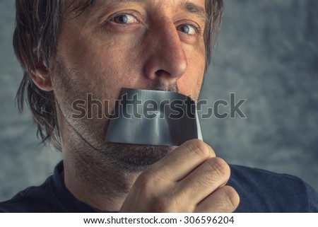 Fighting censorship, adult caucasian man removing duct tape from mouth that prevented him from speaking, freedom of speech and expression concept - stock photo