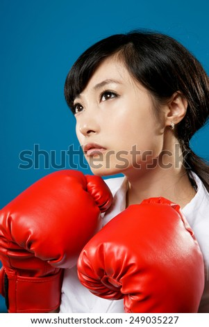 Fighting, closeup portrait of Asian business woman on studio blue background.