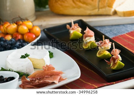 Figs appetizer with prosciutto ham and brie cheese on table of appetizers - stock photo